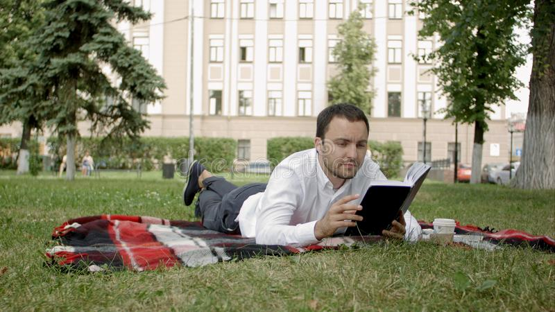 Libro de lectura joven hermoso del hombre de negocios que miente en el parque fotografía de archivo libre de regalías