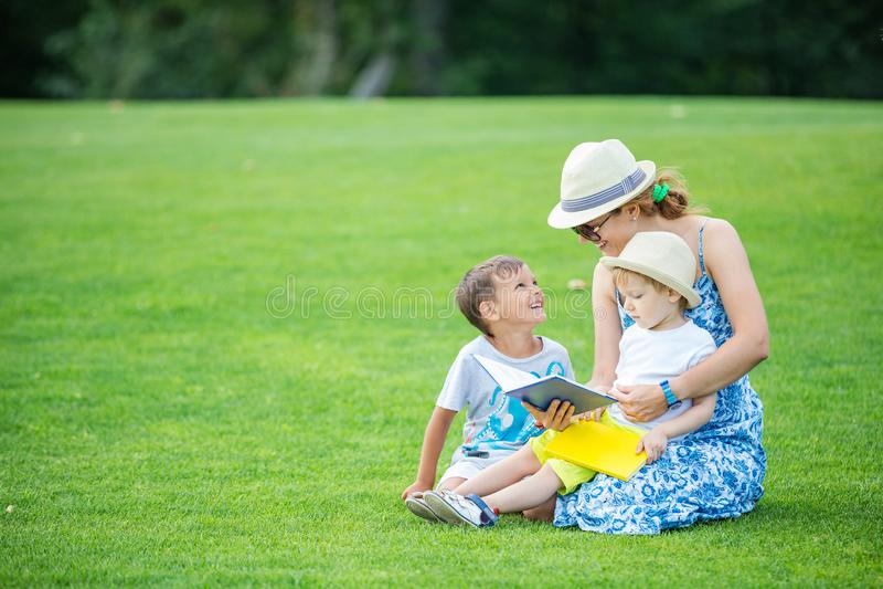 Libro de lectura joven de la madre a sus dos pequeños hijos imagenes de archivo
