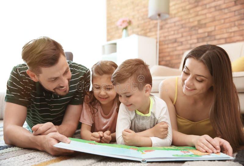 Libro de lectura joven de la pareja con los niños Familia feliz imagen de archivo
