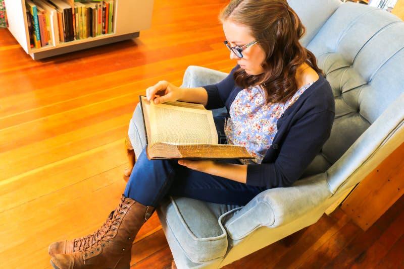 Libro de lectura de la chica joven en la biblioteca fotos de archivo libres de regalías