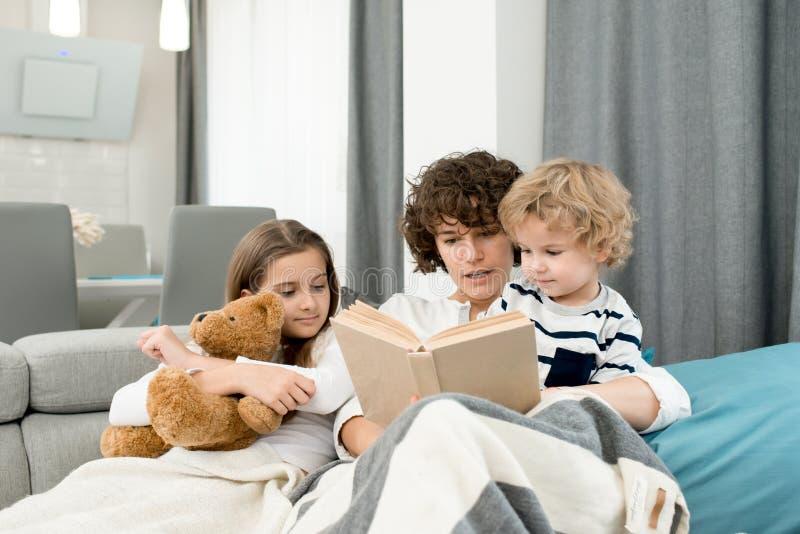 Libro de lectura de la madre a los niños fotografía de archivo libre de regalías