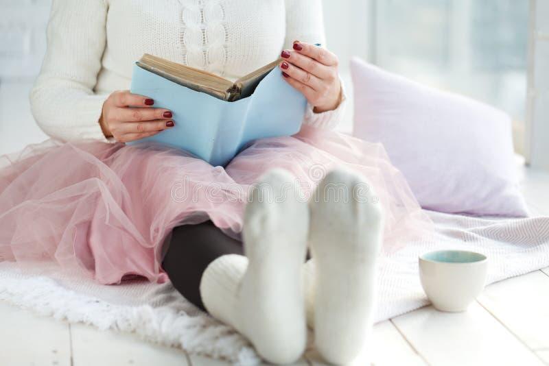 Libro de lectura de la muchacha en cama en un suéter y calcetines calientes que mantienen su café disponible la mañana El humor s imagen de archivo