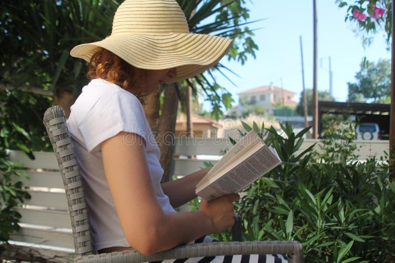 Libro de lectura de la muchacha en el jardín foto de archivo