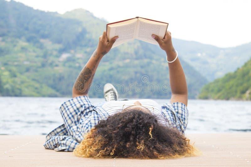 Libro de lectura de la mujer al aire libre fotos de archivo