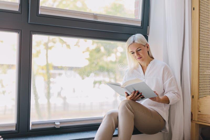Libro de lectura de la mujer en casa por la ventana imagen de archivo libre de regalías
