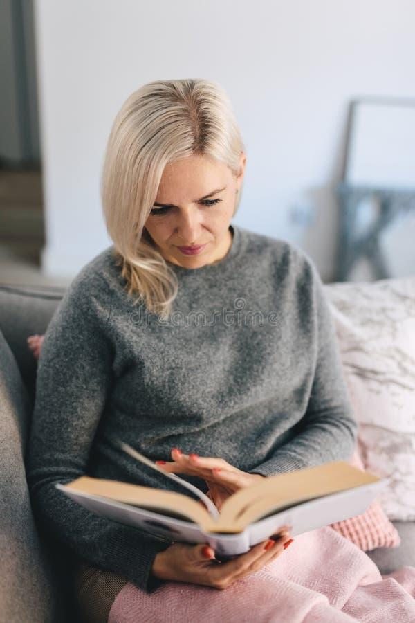 Libro de lectura de la mujer en el sofá fotografía de archivo