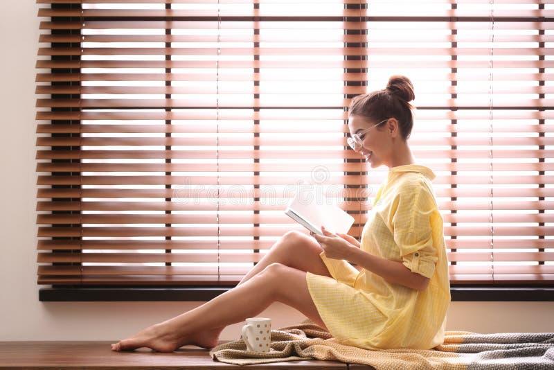 Libro de lectura de la mujer joven cerca de la ventana con las persianas imagenes de archivo
