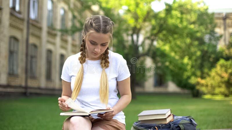 Libro de lectura de la mujer joven en banco en el campus, preparando la preparaci?n, educaci?n imágenes de archivo libres de regalías