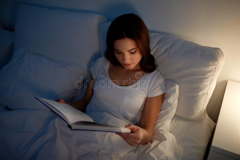 Libro de lectura de la mujer joven en cama en el hogar de la noche fotos de archivo