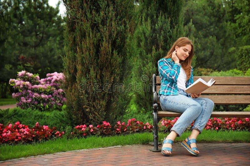 Libro de lectura de la mujer joven mientras que se sienta en banco de madera en parque imagenes de archivo