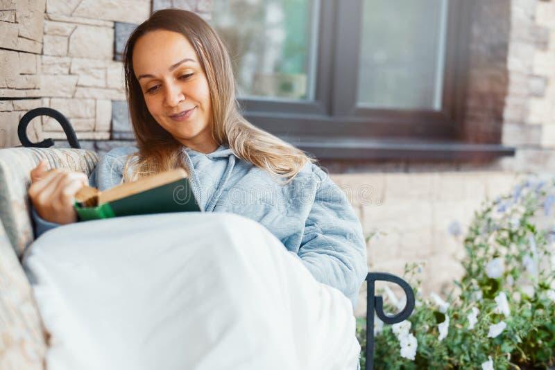 Libro de lectura de la mujer joven y sonrisa al lado de casa grande hermosa fotos de archivo libres de regalías