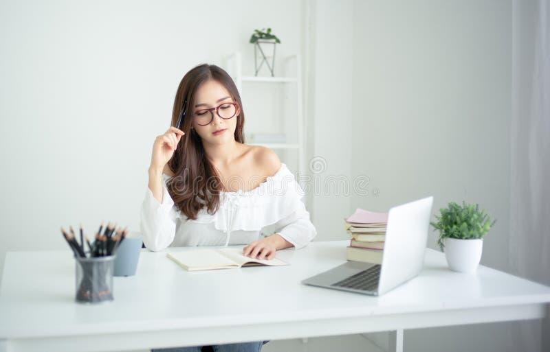 Libro de lectura de la mujer y cabeza asiáticos jovenes pensativos del rasguño con la pluma mientras que se sienta en la tabla co imágenes de archivo libres de regalías
