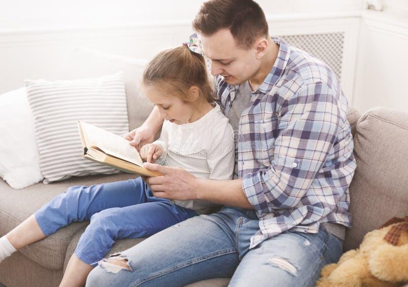 Libro de lectura de la niña con su papá foto de archivo libre de regalías