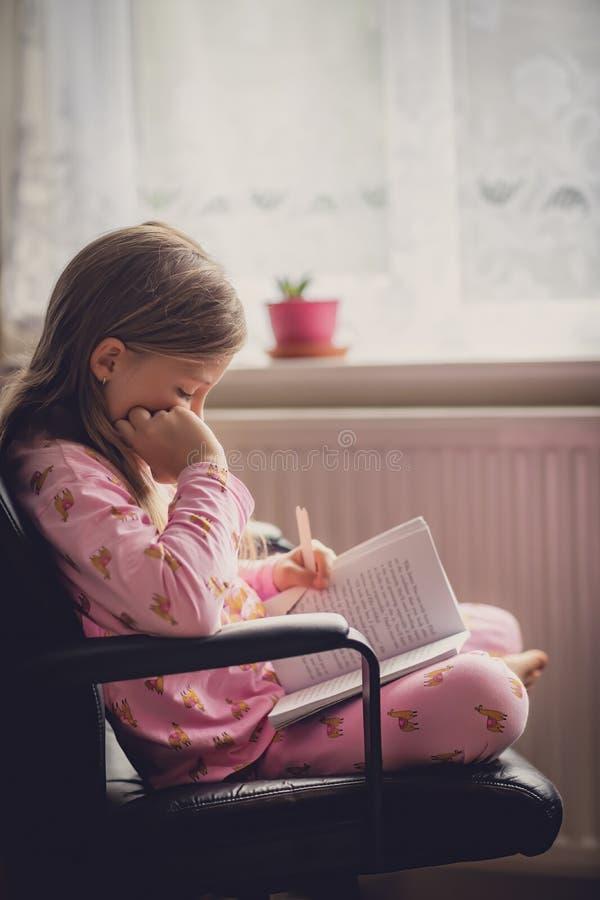 Libro de lectura de la niña por la mañana fotos de archivo