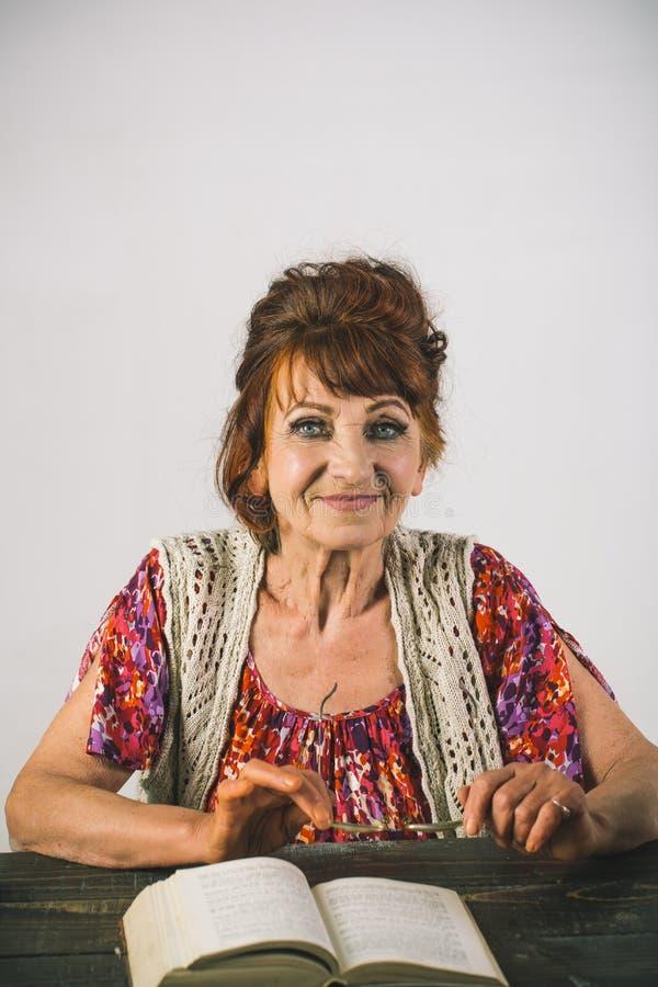 Libro de lectura de la señora mayor con los vidrios fotos de archivo libres de regalías