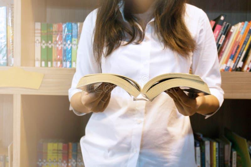 Libro de lectura de las mujeres y relajación en biblioteca Foco selectivo fotos de archivo libres de regalías