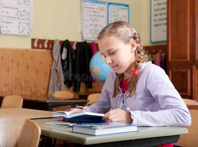 Libro de lectura lindo de la muchacha en sala de clase en la escuela fotos de archivo