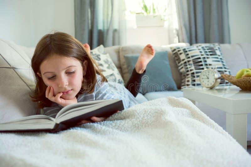 Libro de lectura lindo de la chica joven en casa imagen de archivo libre de regalías