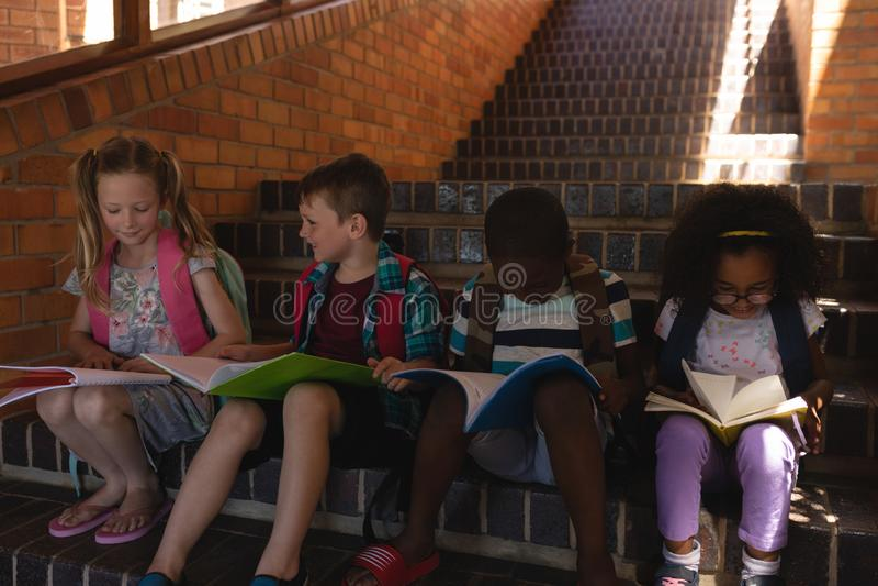 Libro de lectura de los alumnos mientras que se sienta en las escaleras de la escuela primaria fotografía de archivo libre de regalías