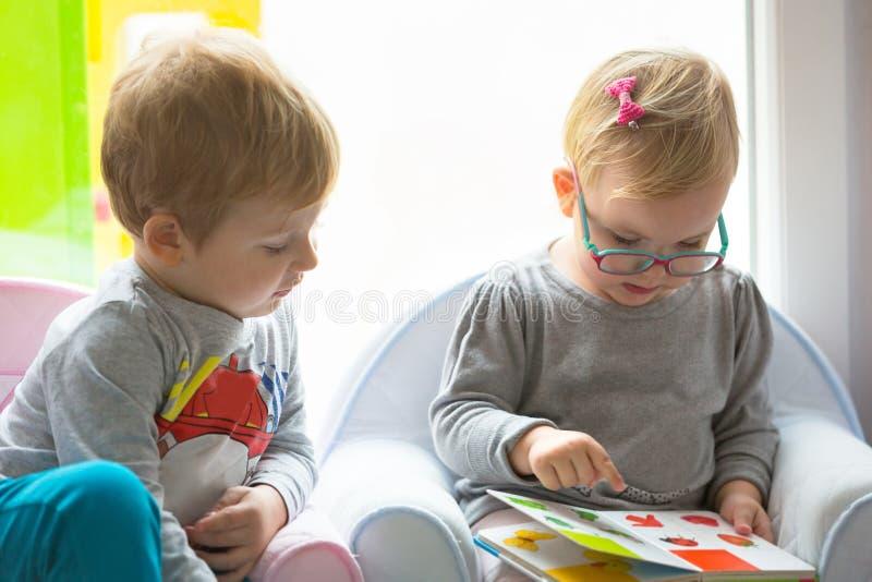 Libro de lectura de los gemelos del muchacho y de la muchacha imagen de archivo libre de regalías