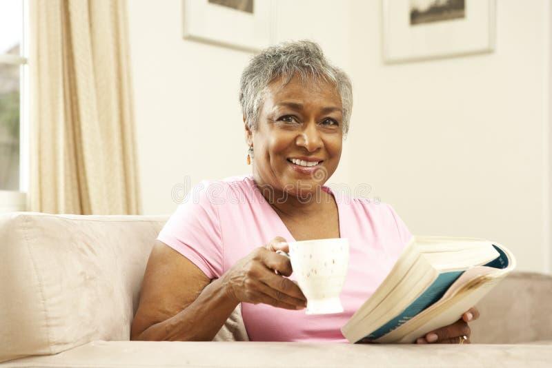 Libro de lectura mayor de la mujer con la bebida fotos de archivo