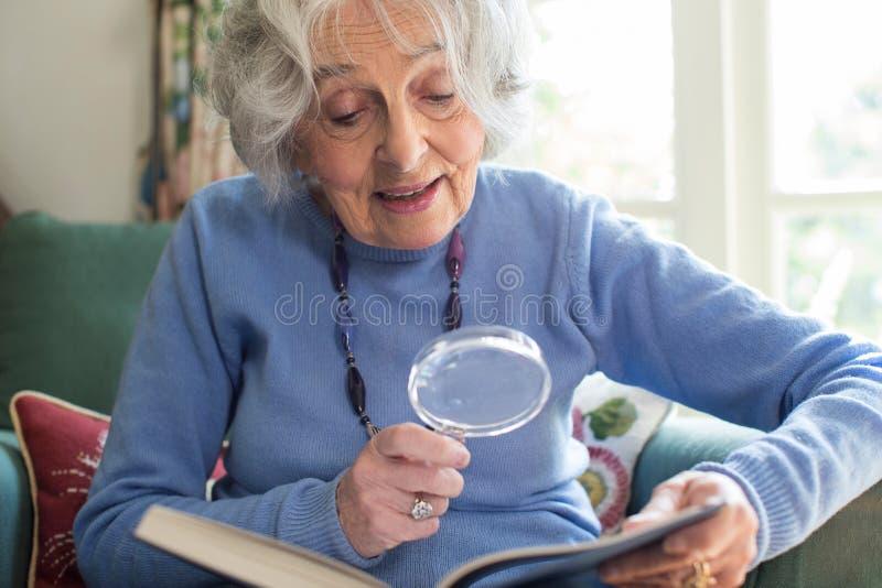 Libro de lectura mayor de la mujer en casa usando la lupa imagen de archivo libre de regalías