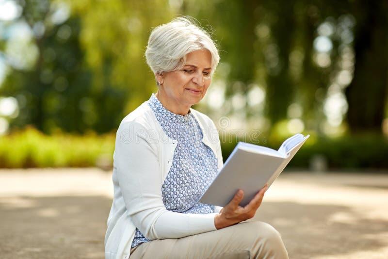 Libro de lectura mayor de la mujer en el parque del verano imágenes de archivo libres de regalías