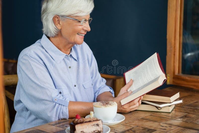 Libro de lectura mayor sonriente de la mujer mientras que se sienta por el café en la tabla fotografía de archivo libre de regalías