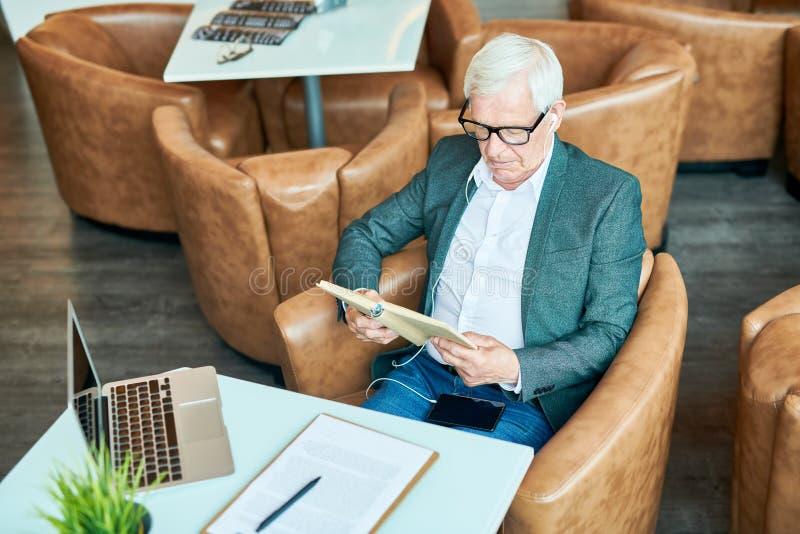 Libro de lectura moderno del hombre mayor en café fotografía de archivo