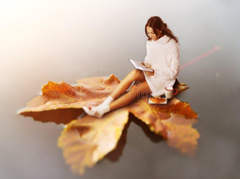 Libro de lectura moreno joven de la mujer, flotando en la hoja fotos de archivo libres de regalías