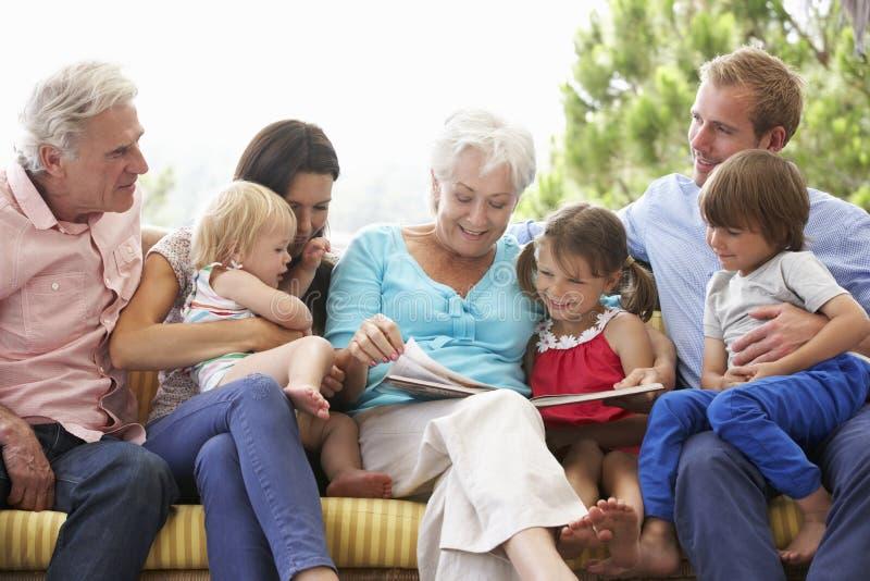 Libro de lectura multi de la familia de la generación en el jardín Seat fotografía de archivo