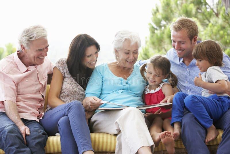 Libro de lectura multi de la familia de la generación en el jardín Seat fotografía de archivo libre de regalías