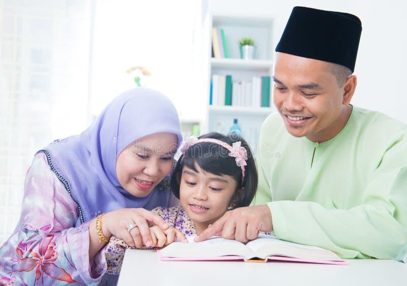 Libro de lectura musulmán de la familia imagen de archivo