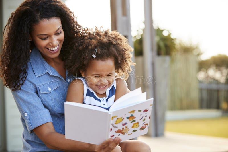 Libro de lectura negro joven de la muchacha que se sienta en rodilla del ½ s del ¿del mumï al aire libre fotos de archivo