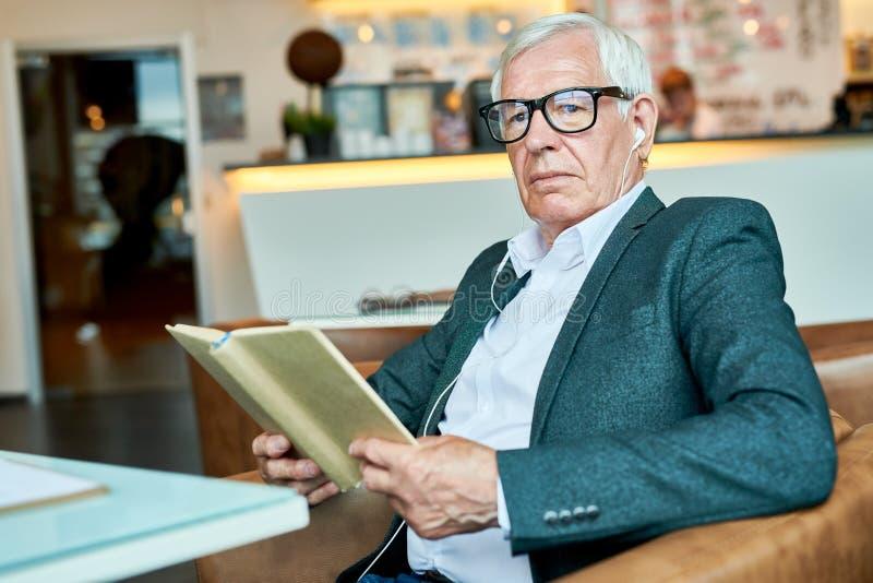 Libro de lectura pensativo del hombre mayor en café imagen de archivo