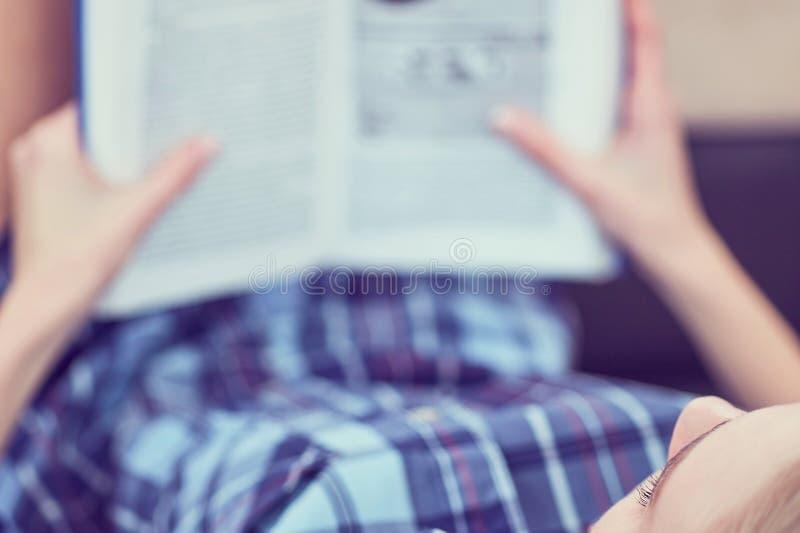 Libro de lectura pensativo de la muchacha Mujer linda joven que estudia en casa, mintiendo en el sofá, espacio de la copia imágenes de archivo libres de regalías