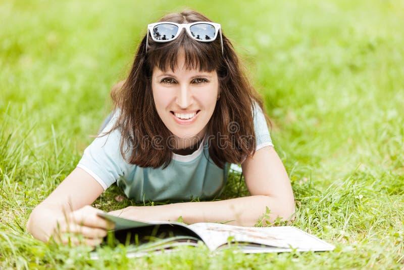 Libro de lectura sonriente de la mujer al aire libre imágenes de archivo libres de regalías