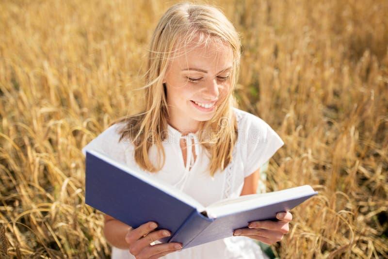 Libro de lectura sonriente de la mujer joven en campo de cereal imagen de archivo libre de regalías