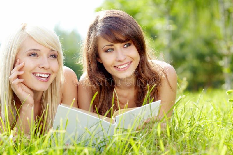 Libro de lectura sonriente hermoso joven de dos mujeres imágenes de archivo libres de regalías