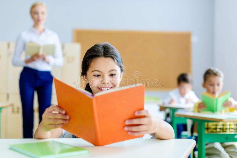 libro de lectura sonriente hermoso de la colegiala en la sala de clase foto de archivo