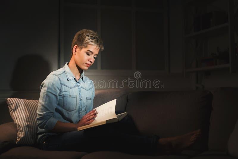 Libro de lectura sonriente de la muchacha del estudiante en sitio oscuro fotos de archivo libres de regalías