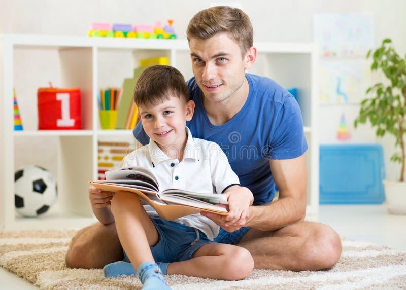 Libro de lectura sonriente lindo del niño en sitio de niños foto de archivo