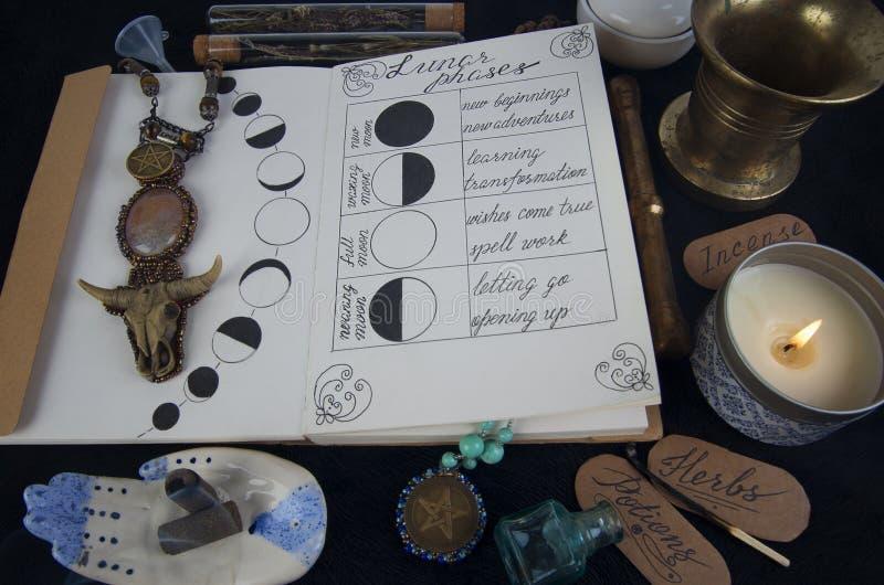 Libro de sombras con fases lunares en el altar negro imagenes de archivo
