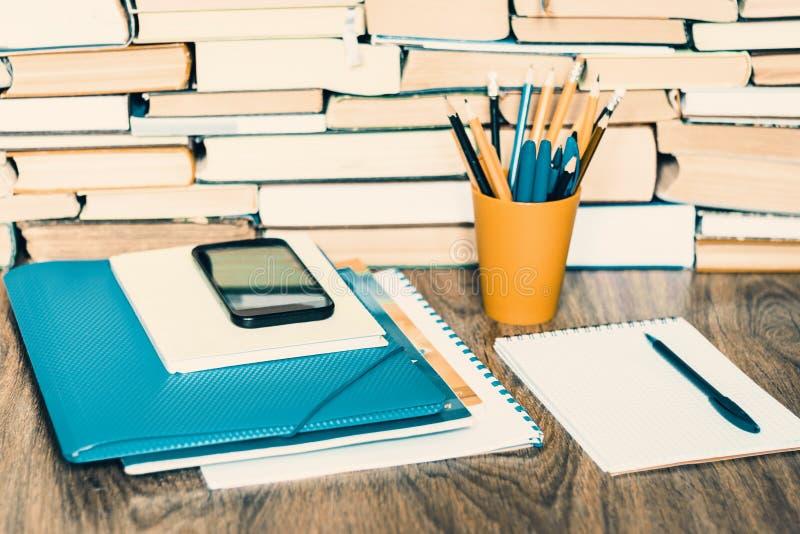 Libro de texto, cuaderno, smartphone, ordenador portátil, vidrios, pilas de la pila de literatura, en el fondo del negocio de la  foto de archivo libre de regalías