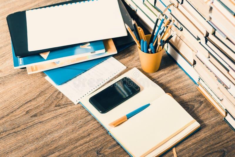 Libro de texto, cuaderno, smartphone, ordenador port?til, vidrios, pilas de la pila de literatura, en el fondo del negocio de la  imágenes de archivo libres de regalías