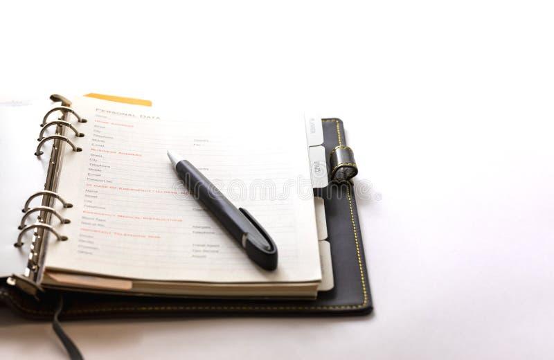 Libro del pianificatore aperto sui precedenti bianchi con una penna nera immagine stock libera da diritti