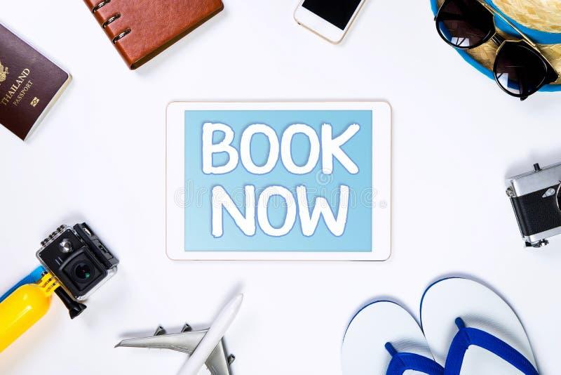 Libro del viaje en línea ahora en la tableta para la agencia de viajes en línea imagenes de archivo