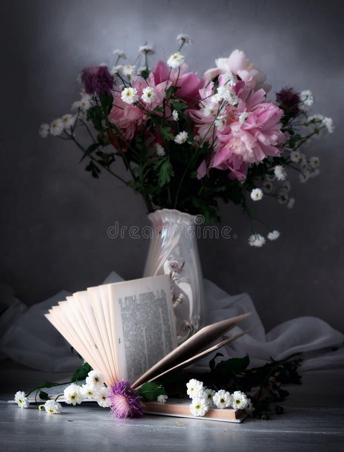 Libro del vintage con el ramo de flores al lado del florero con las flores fondo romántico nostálgico del vintage imagenes de archivo