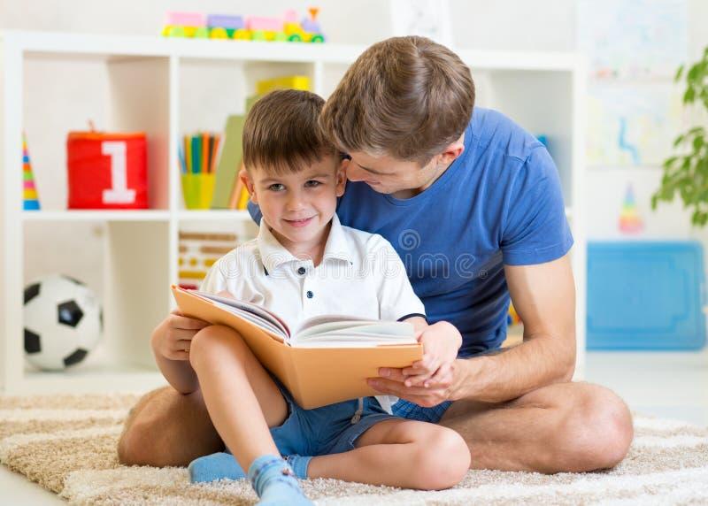 Libro di bambini della lettura del papà per scherzare ragazzo fotografia stock