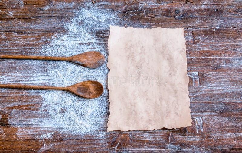 Libro di cucina in bianco con alcuni ingredienti sulla tavola di legno fotografia stock libera da diritti